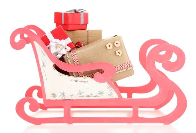 白で隔離のクリスマスプレゼントと木のおもちゃのそり