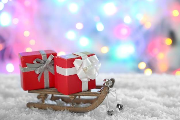 Деревянные игрушечные санки с рождественскими подарками на блестящей поверхности