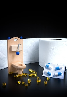 Wooden toy toilet, capsules and paper on black background