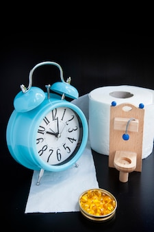 Wooden toy toilet, pills and alarm clock on black