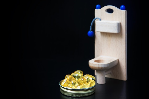 Wooden toy toilet and yellow capsules