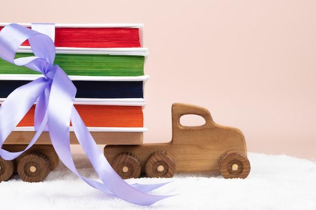 Деревянный игрушечный грузовик и стопка книг. рождественский подарок концепции. фото высокого качества
