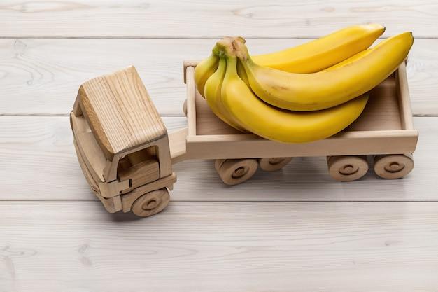Деревянный игрушечный грузовик везет связку бананов. вид сверху, студийный снимок.