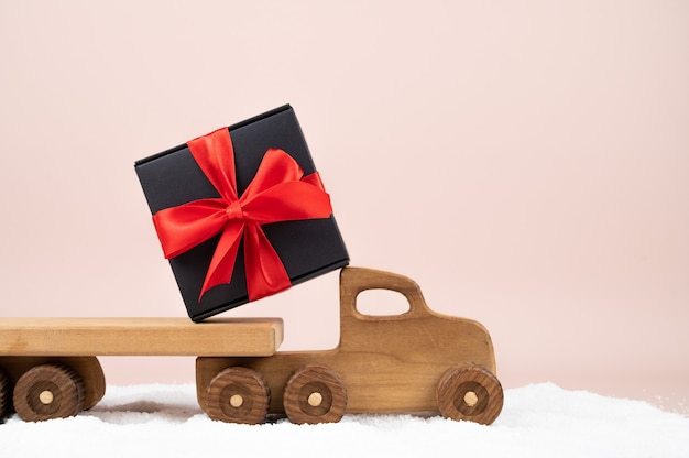 Деревянная тележка игрушки с подарочной коробкой рождества на розовой предпосылке. карта праздников. фото высокого качества