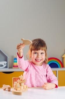木のおもちゃのコンセプト。子供部屋のテーブルの上で木のおもちゃのロケットで遊ぶ美しい少女。