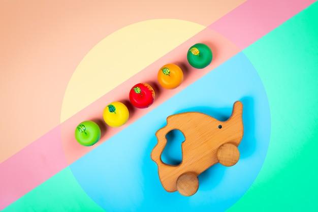 격리 된 여러 가지 빛깔의 활기찬 기하학적 배경에 화려한 사과와 나무 장난감 고슴도치
