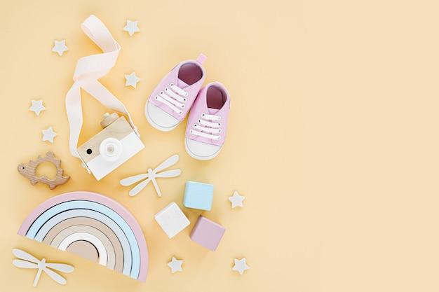 黄色の背景に生まれたばかりの女の子のための木のおもちゃ、ピンクのスリッパと虹。ベビー用品とアクセサリーのセット。フラットレイ、上面図