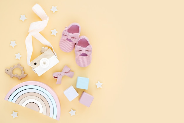 Wooden toys, pink slippers and rainbow for newborn girl on yellow background.  set of  baby stuff and accessories. flat lay, top view