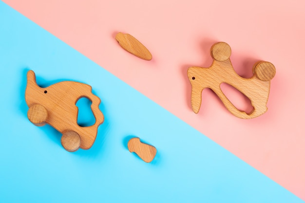 Wooden toys rabbit with carrot, hedgehog with mushroom  on an isolated multicolored vibrant geometric background.