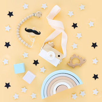 Wooden toys with rainbow and toy camera for kids on yellow background.  set of  baby stuff and accessories. flat lay, top view