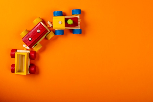 Wooden train on orange background with space for text.