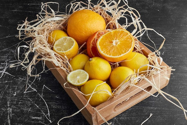 A wooden tray of citrus fruits.