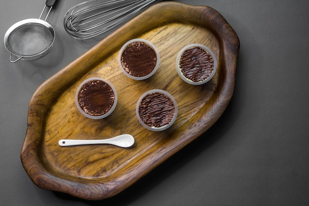 The wooden tray contains 4 cups of tiramisu.