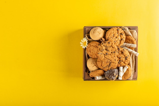 A wooden tray of cookies on yellow