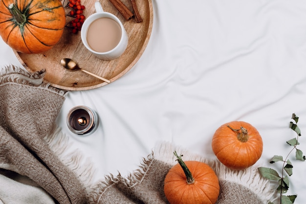 Wooden tray, cup of coffee or cocoa, candle, pumpkins on white sheets and blankets