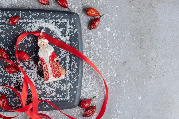Wooden tray. hips, red ribbons, scissors, coconut powder and santa figurine on marble table.
