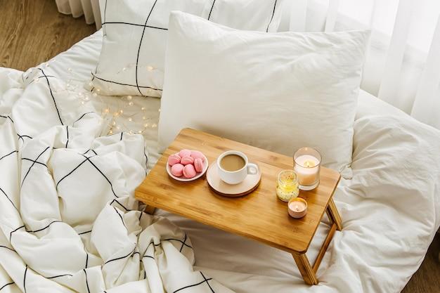 침대에 커피와 촛불의 나무 쟁반입니다. 줄무늬 담요와 베개가 있는 흰색 침구 시트. 침대에서 아침 식사. 휘게 컨셉.