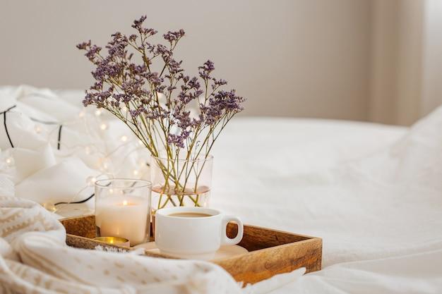 침대에 꽃과 함께 커피와 촛불의 나무 쟁반. 줄무늬 담요와 베개가 있는 흰색 침구 시트. 침대에서 아침 식사. 휘게 컨셉.