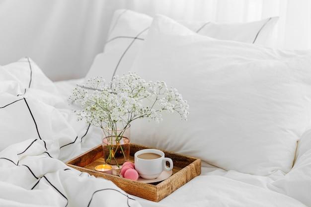 Деревянный поднос с кофе и свечами с цветами на кровати. белые простыни с полосатым одеялом и подушкой. завтрак в постель. концепция hygge.