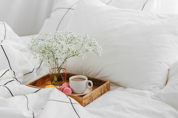 Деревянный поднос с кофе и свечами с цветами на кровати. белые простыни с полосатым одеялом и подушкой. оставайся дома, на карантин.