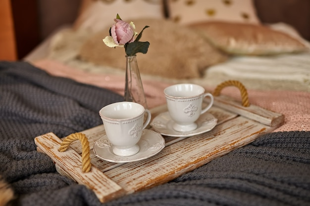 ベッドの上に花とコーヒーの木製トレイ。さまざまな暖かい毛布と枕が付いたロマンチックなベッド。外出禁止令、検疫。