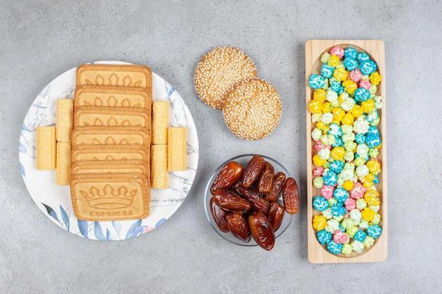 Vassoio in legno di caramelle popcorn, una piccola porzione di datteri, due biscotti e biscotti allineati su un piatto su fondo di marmo. foto di alta qualità