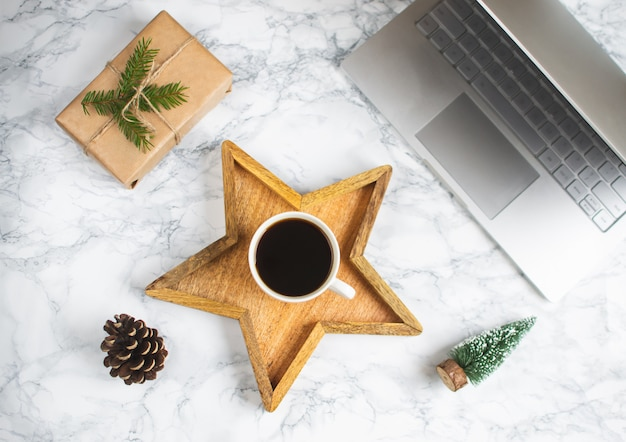 Wooden tray star cup with black coffee christmas morning gift box laptop new year concept