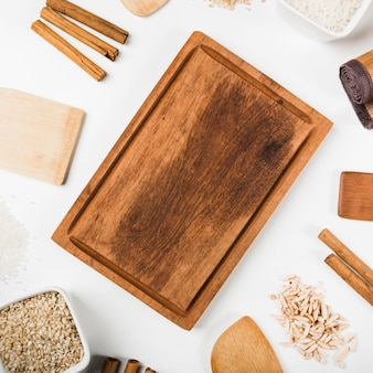 Wooden tray surrounded with uncooked rice; cinnamon sticks; spatula on white background