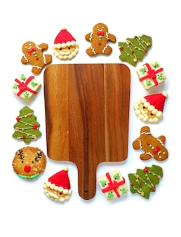 Wooden tray surrounded with variety of christmas cookies on a white background