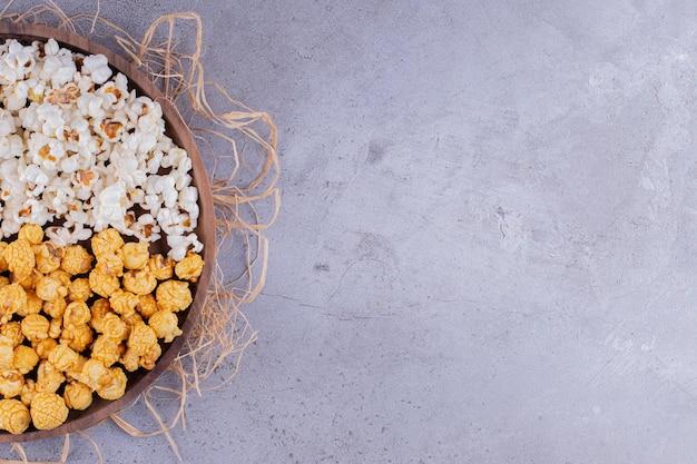 Деревянный поднос с ассортиментом попкорна на груде соломы на мраморном фоне. фото высокого качества