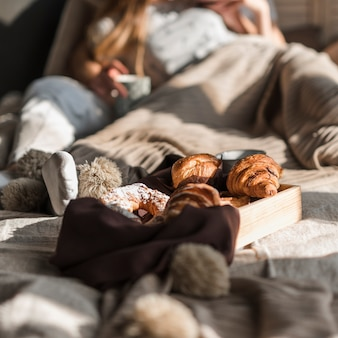 Wooden tray with baked croissant in front of couple lying on bed
