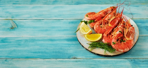 A wooden tray with bif argentinian prawns on vintage blue background
