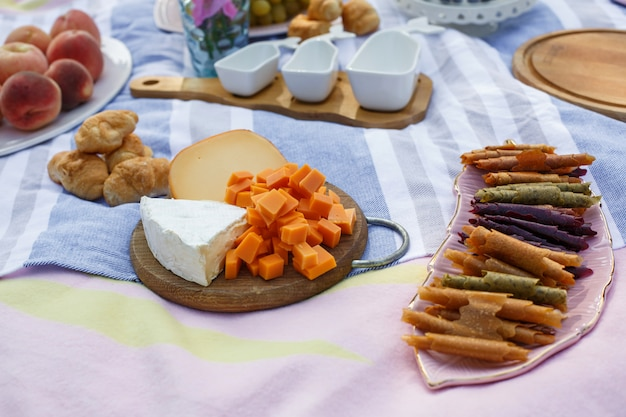 Wooden tray with cheese assorti, pastillum rolls and croissant layout on blue picnic blanket