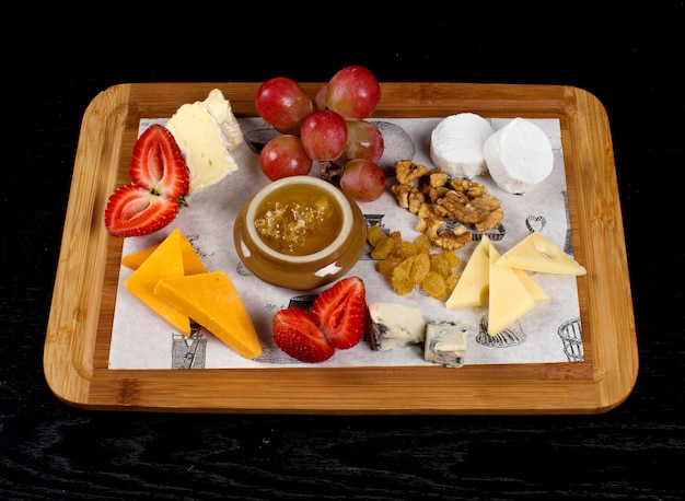 Wooden tray with cheeses, fruits and a jar of honey
