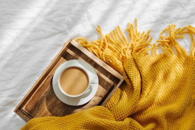 Деревянный поднос с кофе и теплый плед на белых постельных принадлежностях. завтрак в постель. концепция hygge.