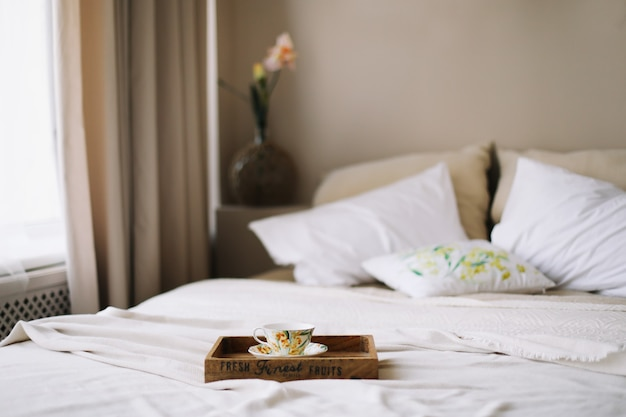 Wooden tray with coffee cup in bed