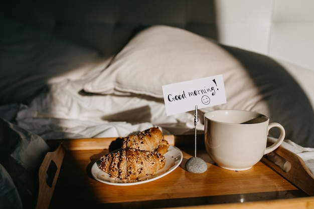 A wooden tray with croissants and cup of coffee on bed