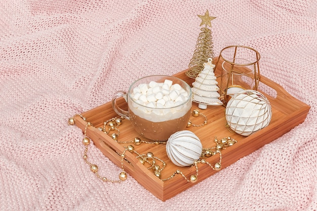 Wooden tray with cup of cocoa, marshmallows and christmas decorations on warm knitted pink plaid.