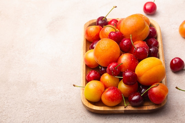 Деревянный поднос со свежей вишней, сливами и абрикосами с каплями воды