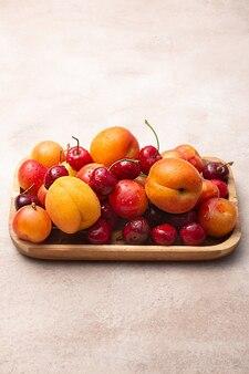 Деревянный поднос со свежей вишней, сливами и абрикосами