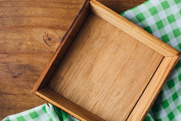 Wooden tray with green table cloth on wooden background