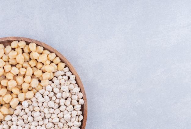 大理石の表面に生と調理済みのひよこ豆の半分を満たした部分が付いた木製トレイ