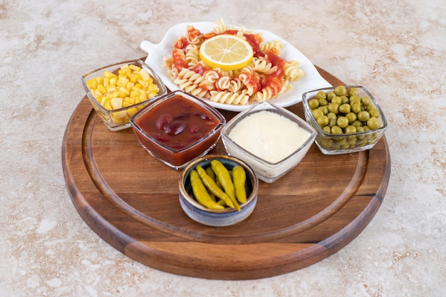Wooden tray with pasta serving and bowls of toppings and dressings on marble surface.