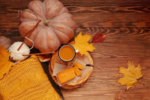 カボチャのパイとフレーバーコーヒーが入った木製トレイ、白いマグカップの上面図、または...