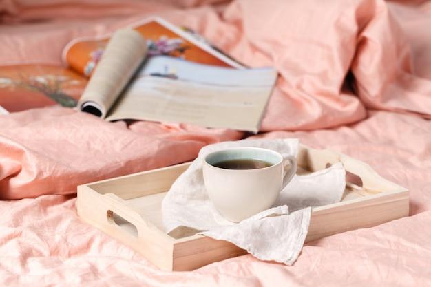 ベッドの上のおいしい朝食付きの木製トレイ