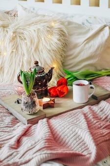 居心地の良いベッドの上にお茶と春の花が付いた木製トレイ、縦の写真。朝食のコンセプト。高品質の写真