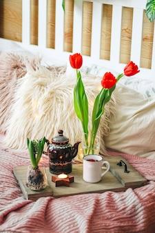 居心地の良いベッドの上にお茶と春の花が付いた木製トレイ、縦の写真。高品質の写真