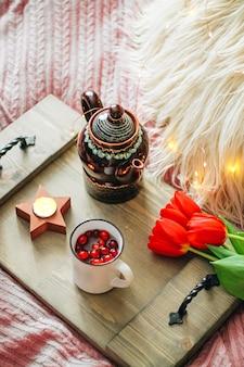 Деревянный поднос с чаем и тюльпанами на уютной кровати, фото вертикальное. фото высокого качества