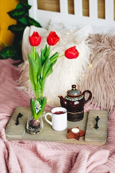 Wooden tray with tea and bouquet of tulips on a cozy bed, vertical photo. high quality photo