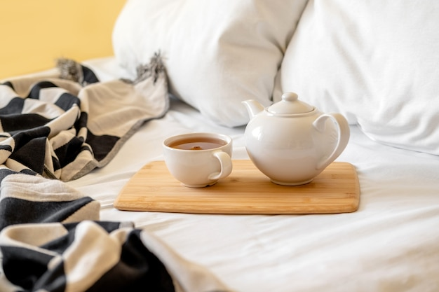 Wooden tray with tea cup and teapot